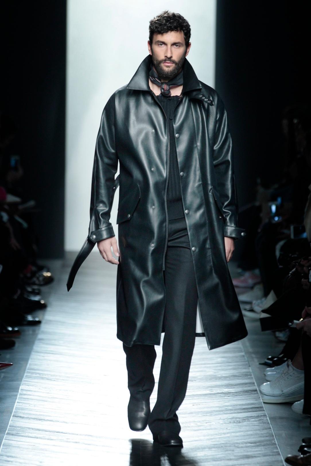 Noah trägt einen schwarzen Mantel aus beschichtetem Polyester, darunter einen schwarzen Pullover aus Wolle und Kaschmir; Hose und Schuhe ebenfalls aus Kaschmir – die schwarzen Stiefel sind aus Kalbsleder